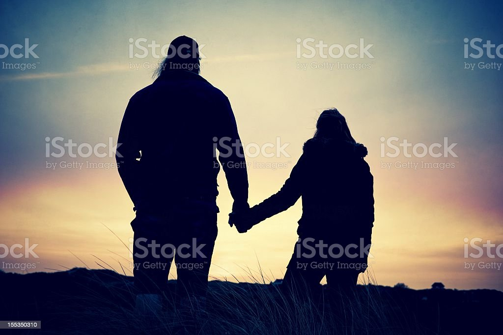 Couple Holding Hands, Silhouette, Sunset royalty-free stock photo