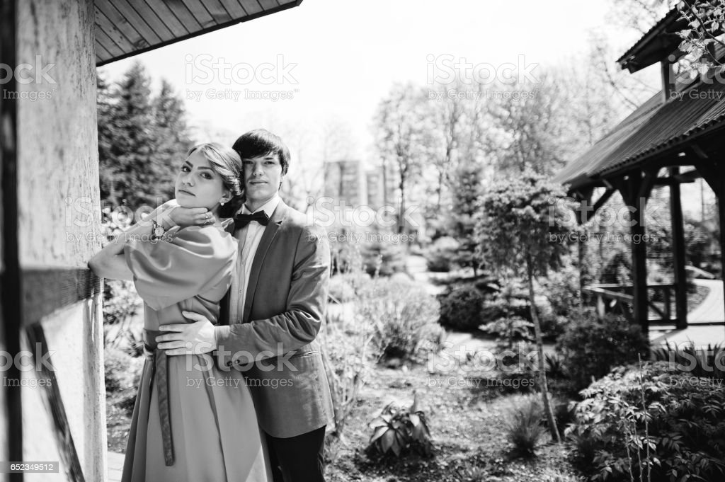 Couple holding hands. Stylish man at velvet jacket and girl in red dress in love together. Black and white photo stock photo