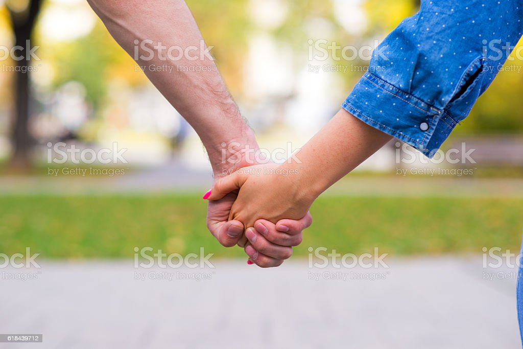 Couple Holding Hands Walking Away outside stock photo