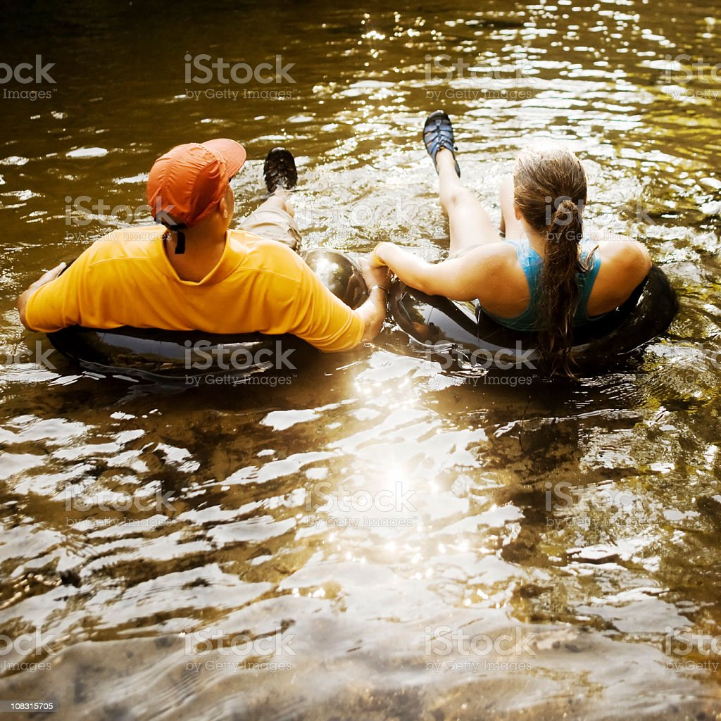 Couple Holding Hands While Floating on Inner Tubes stock photo