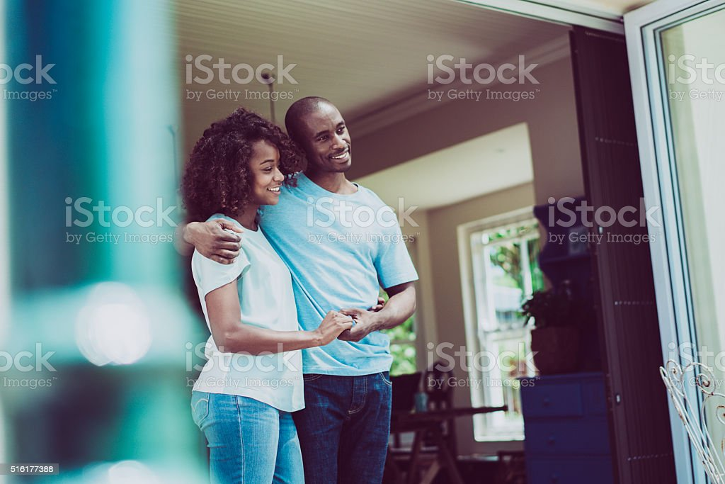 Couple holding hands while looking away at entrance stock photo
