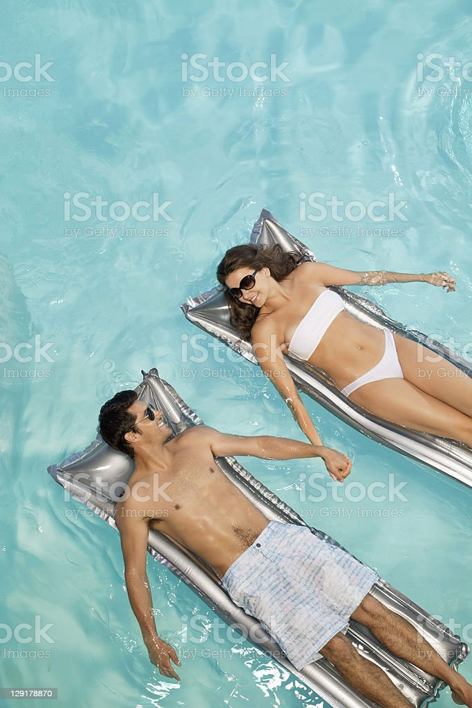 Couple holding hands while lying on raft royalty-free stock photo