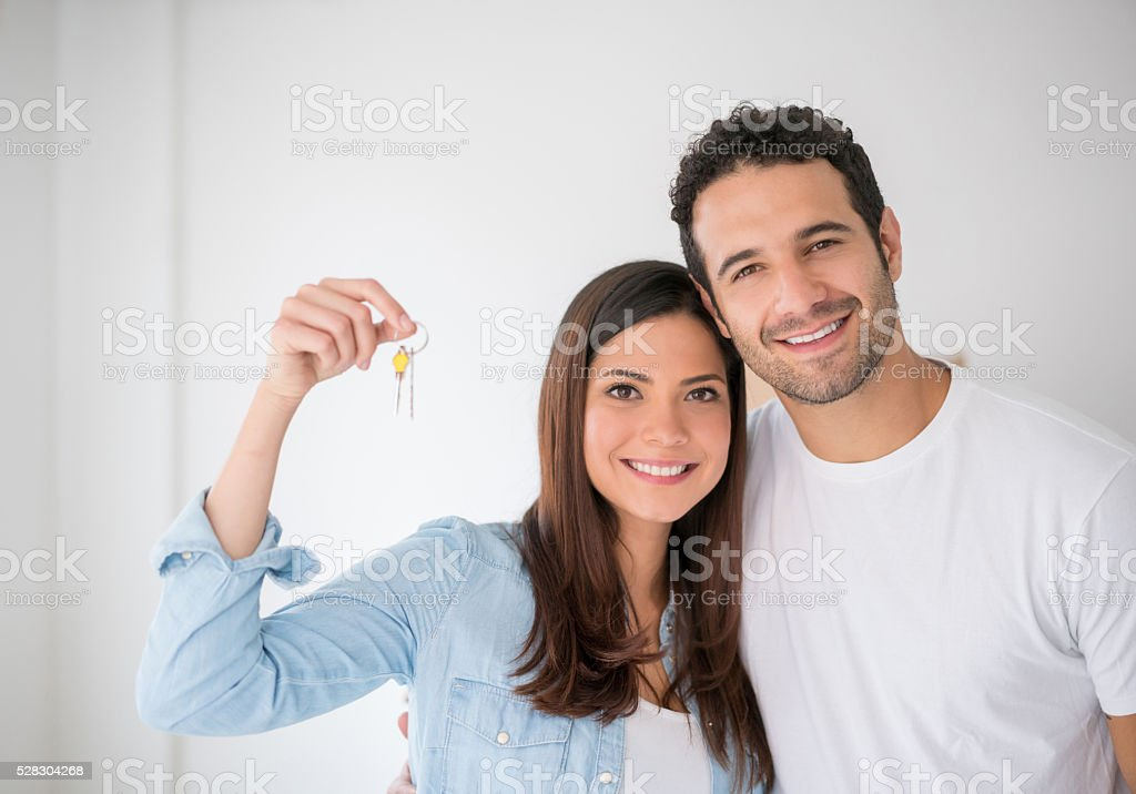 Couple holding keys to their new house stock photo