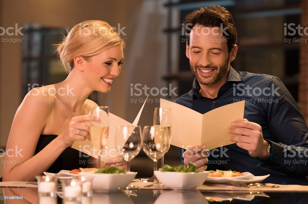 Couple holding menu cards stock photo