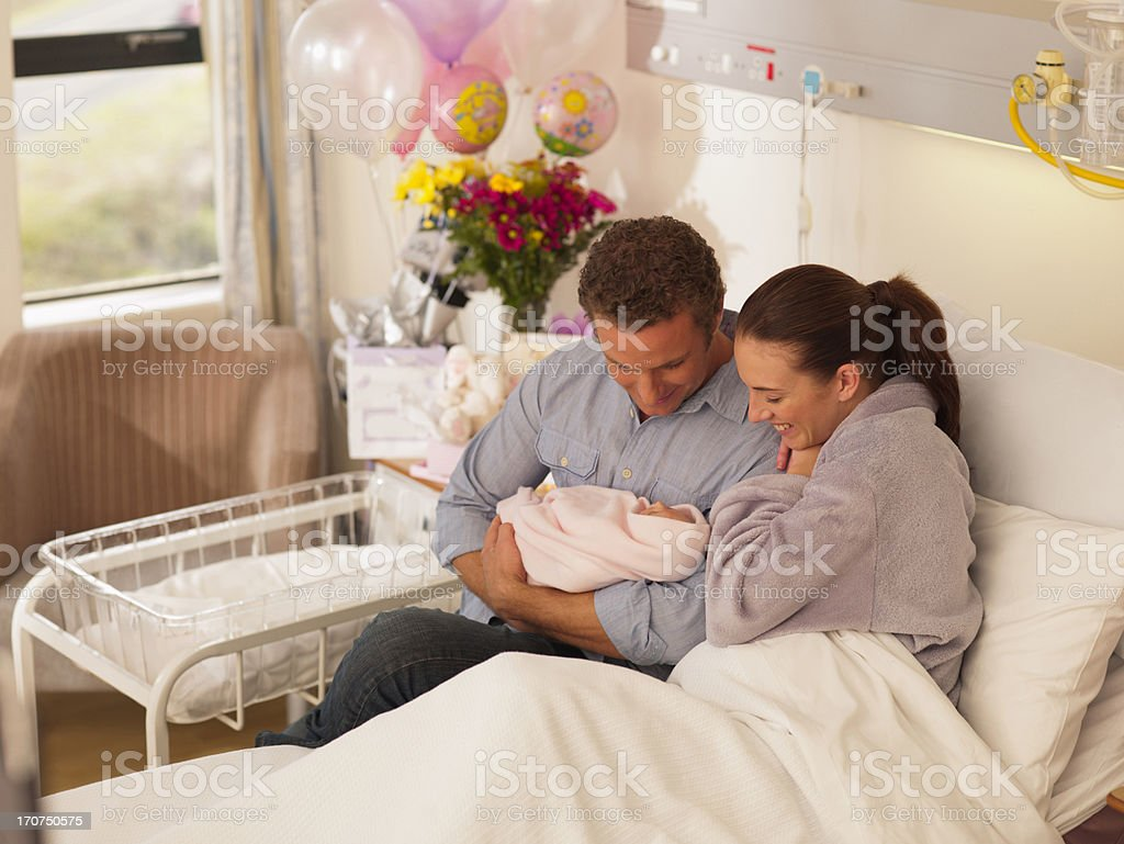 Couple holding newborn baby in hospital stock photo