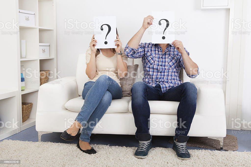 Couple Holding Question Mark Sign In Front Of Face royalty-free stock photo