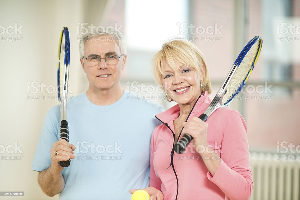 Couple holding tennis rackets stock photo