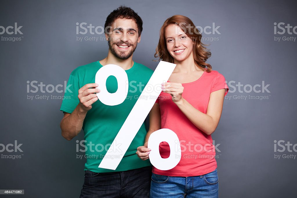Couple holding three dimensional percentage sign stock photo