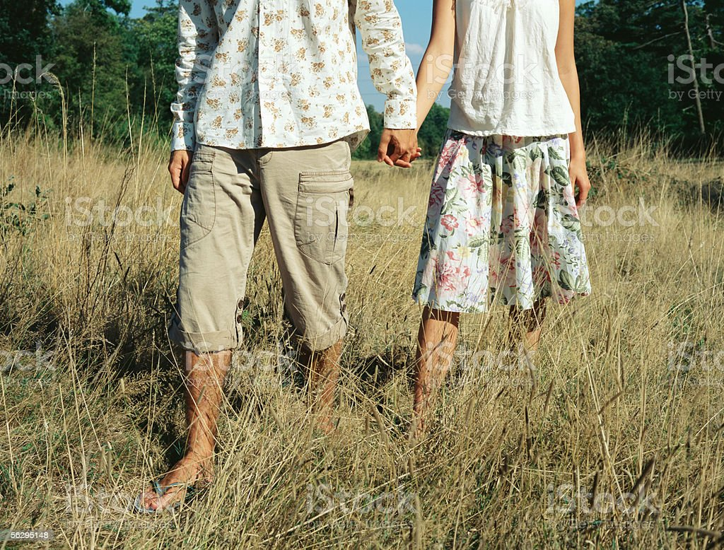 Couple holding walking hand in hand stock photo