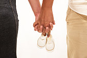 Couple holds baby shoes