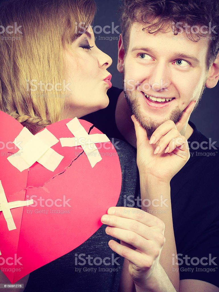 Couple holds broken heart joined in one stock photo