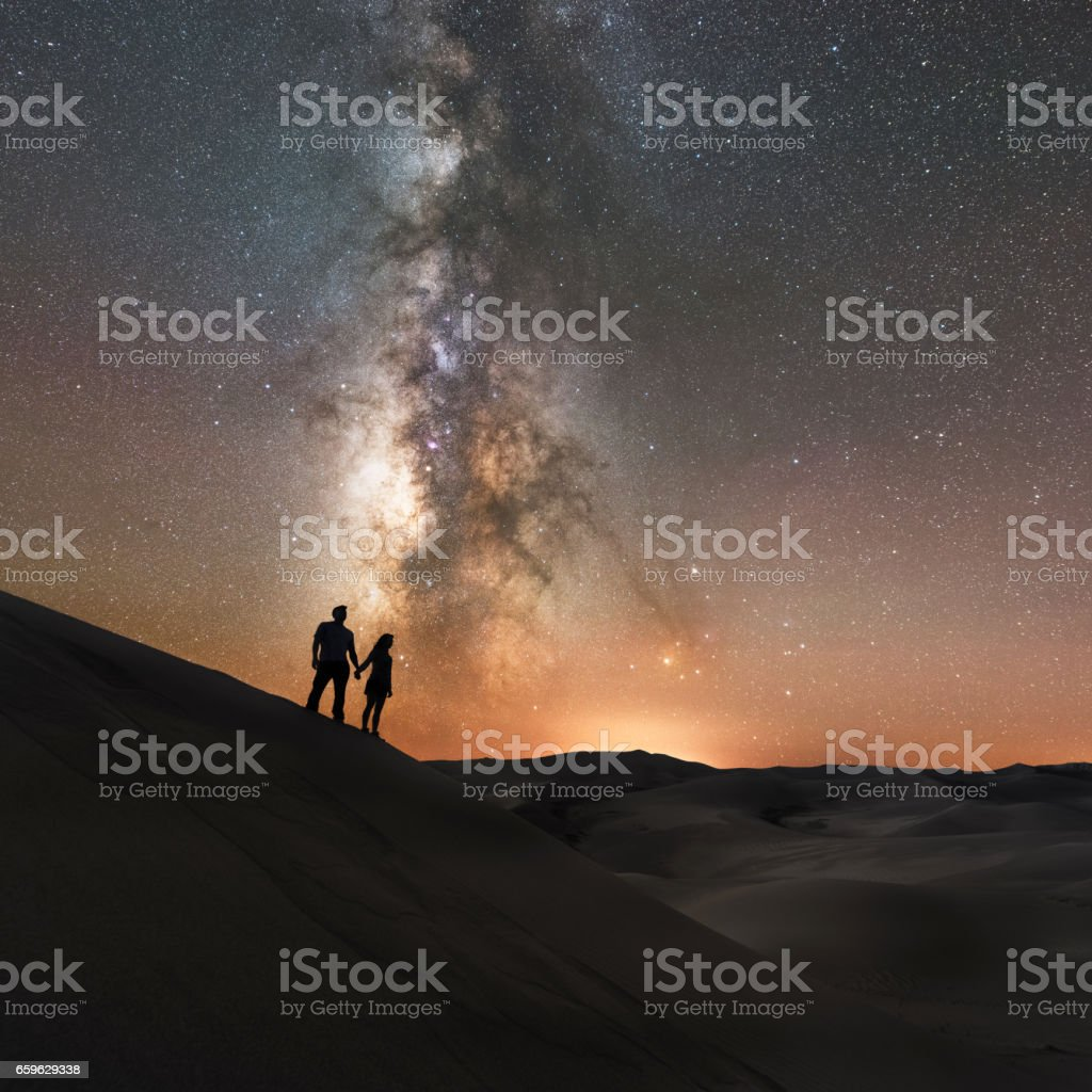 A couple holds hands under the Milky Way Galaxy stock photo