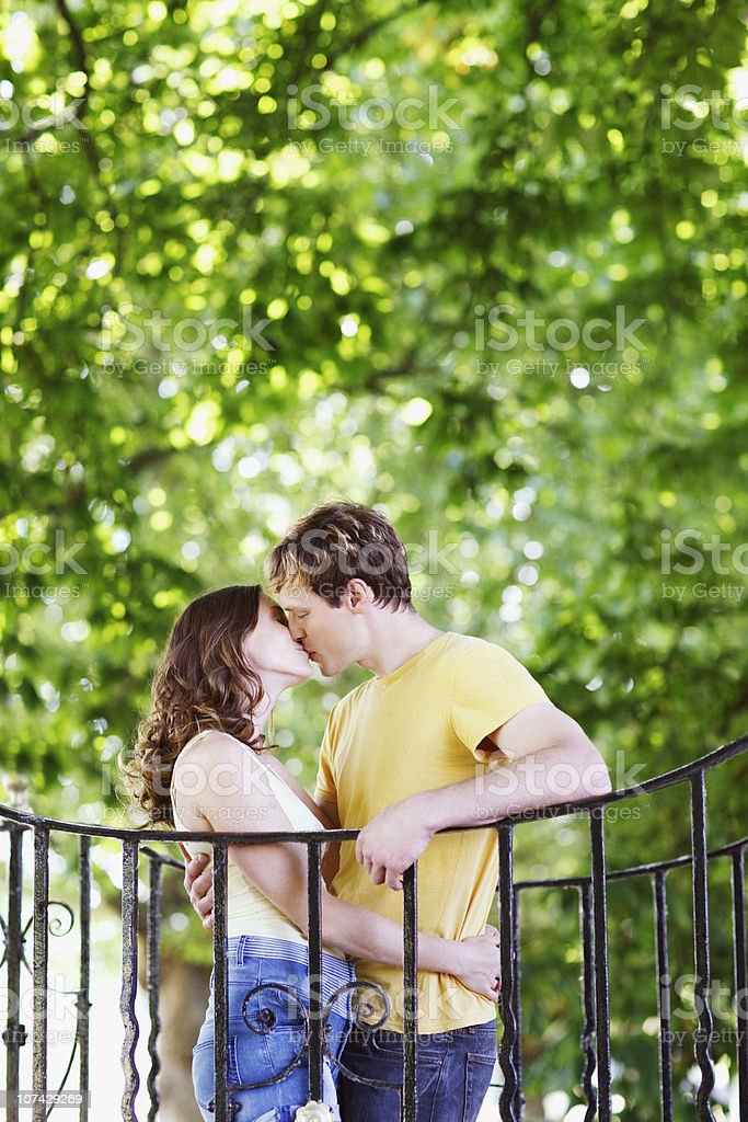 Couple hugging and kissing near railing outdoors royalty-free stock photo