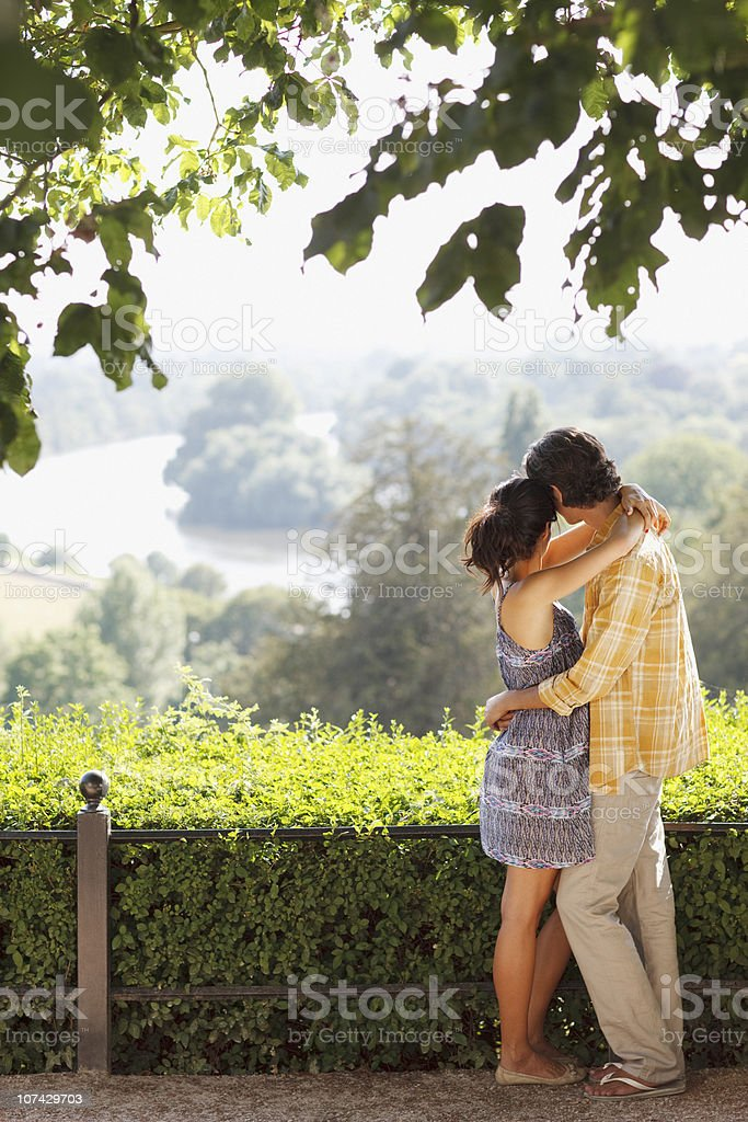 Couple hugging and looking at landscape royalty-free stock photo