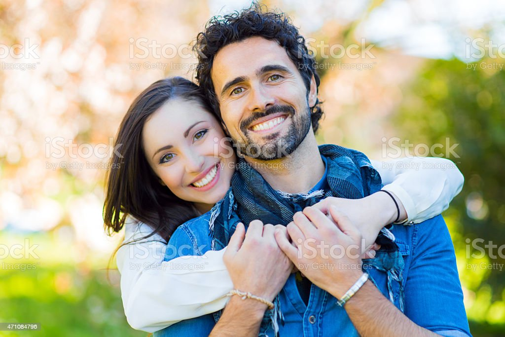 Couple hugging and smiling outdoors stock photo