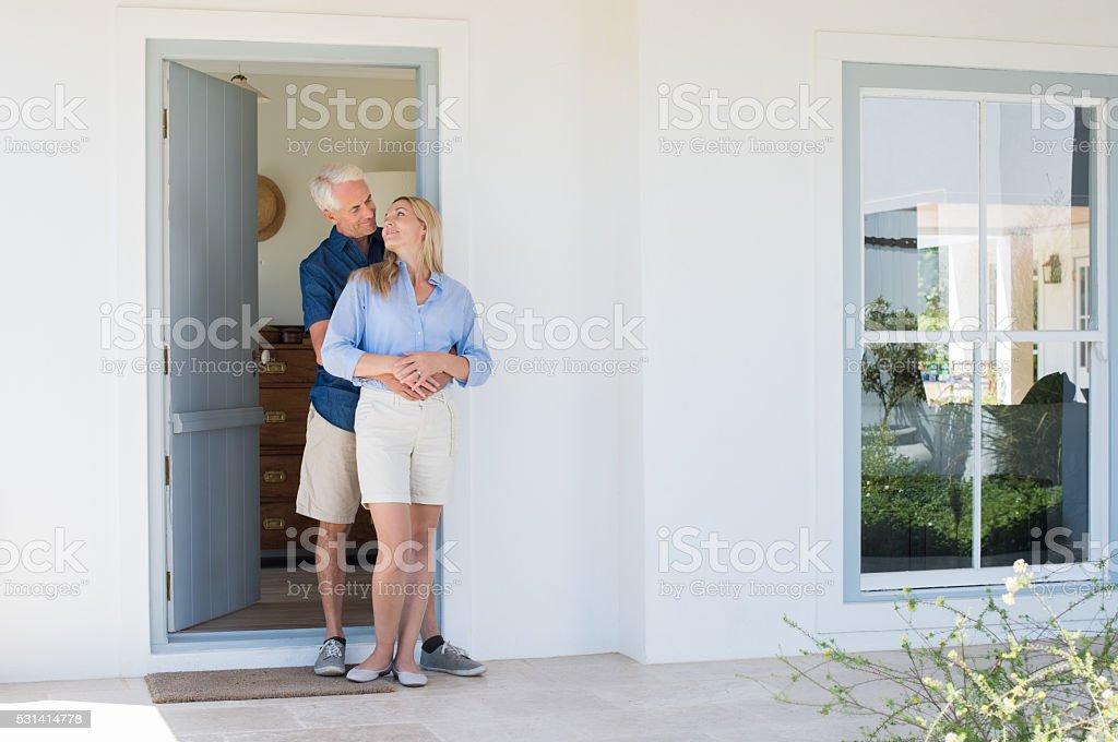 Couple hugging at door stock photo