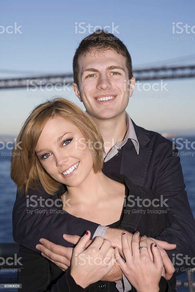 Couple hugging by Bay Bridge royalty-free stock photo