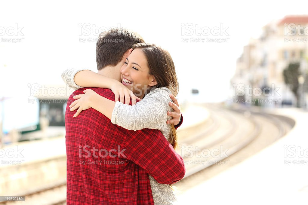 Couple hugging happy in a train station stock photo
