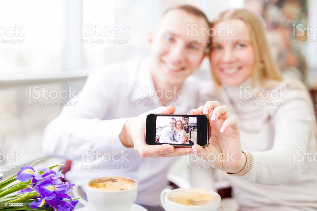 couple hugging in cafe and taking selfie with smartphone stock photo