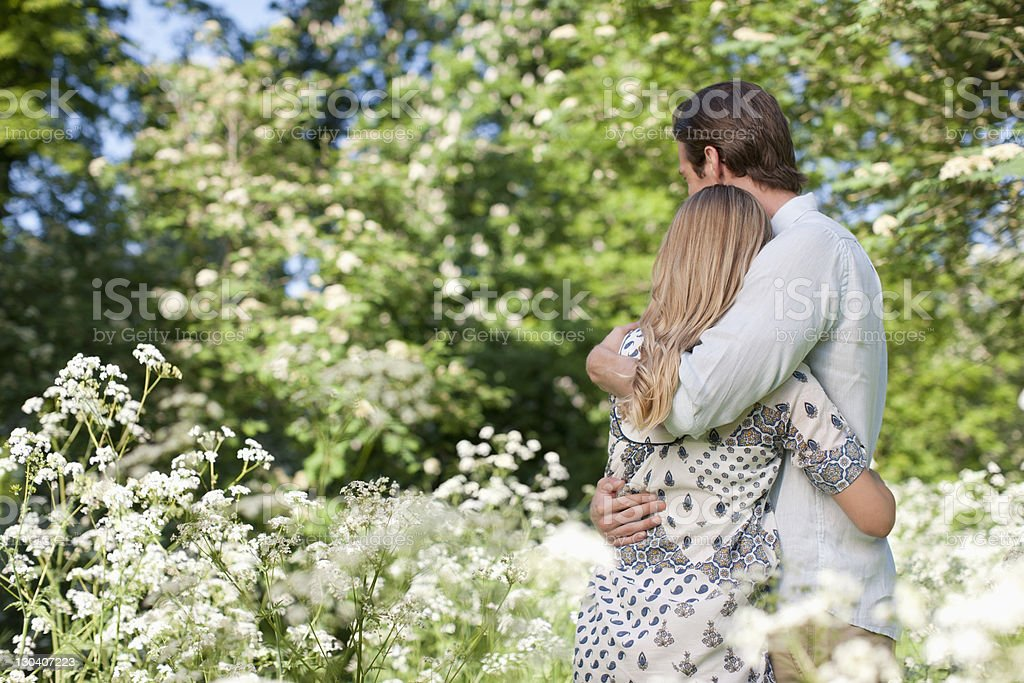 Couple hugging in field of flowers royalty-free stock photo