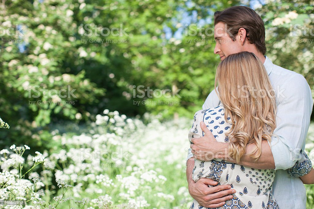 Couple hugging in field of flowers stock photo
