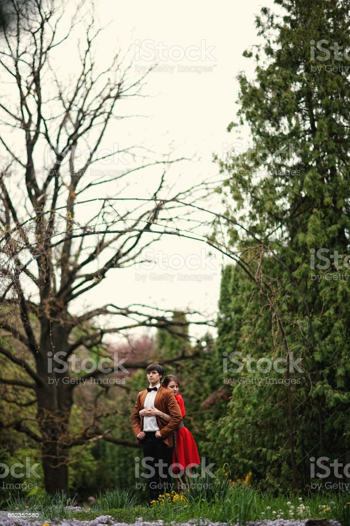 Couple hugging in love at park garden background big arch. Stylish man at velvet jacket and girl in red dress in love together stock photo