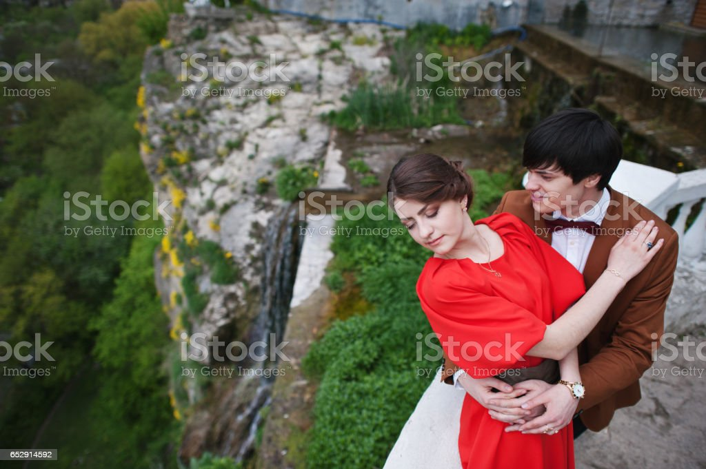 Couple hugging in love background fantastic cliff with waterfall. Stylish man at velvet jacket and girl in red dress in love together stock photo