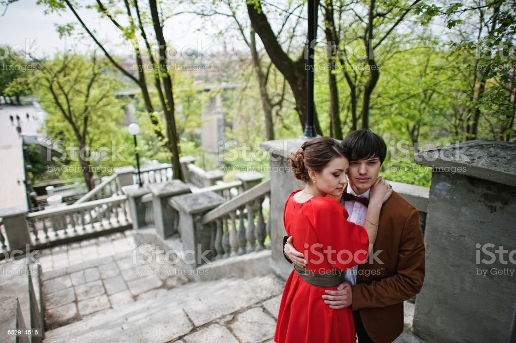 Couple hugging in love background stairs of park bridge. Stylish man at velvet jacket hold inf hands girl in red dress. stock photo