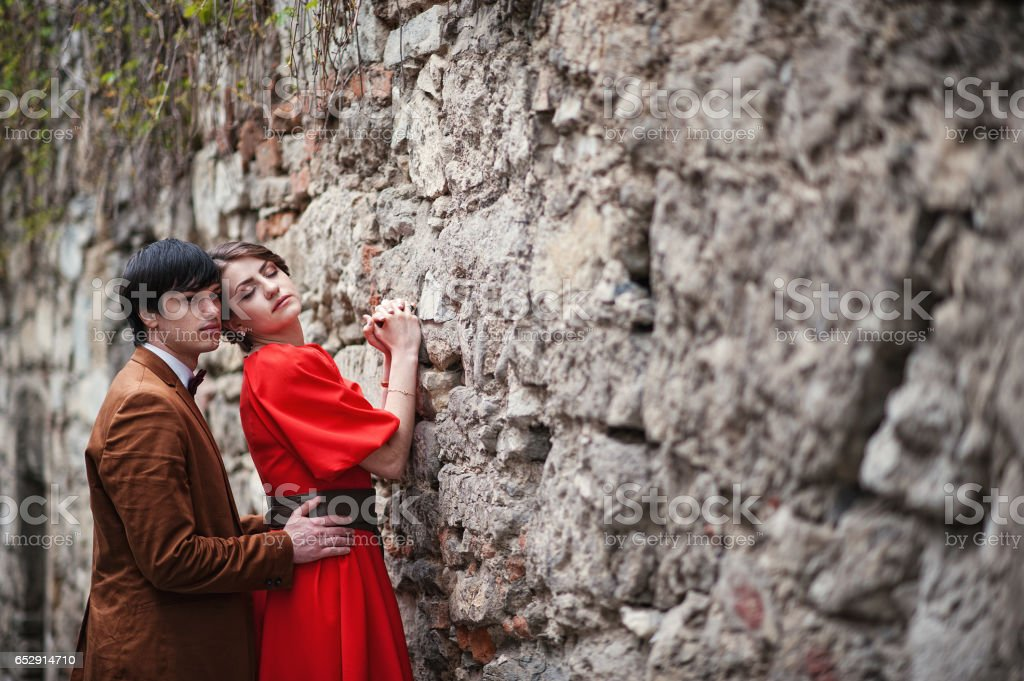 Couple hugging in love background stone wall of castle. Stylish man at velvet jacket and girl in red dress in love together stock photo