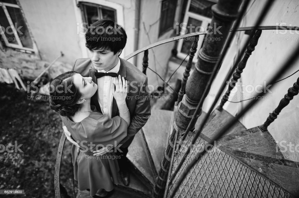 Couple hugging in love background twisted staircase to the balcony. Stylish man at velvet jacket and girl in red dress in love together stock photo