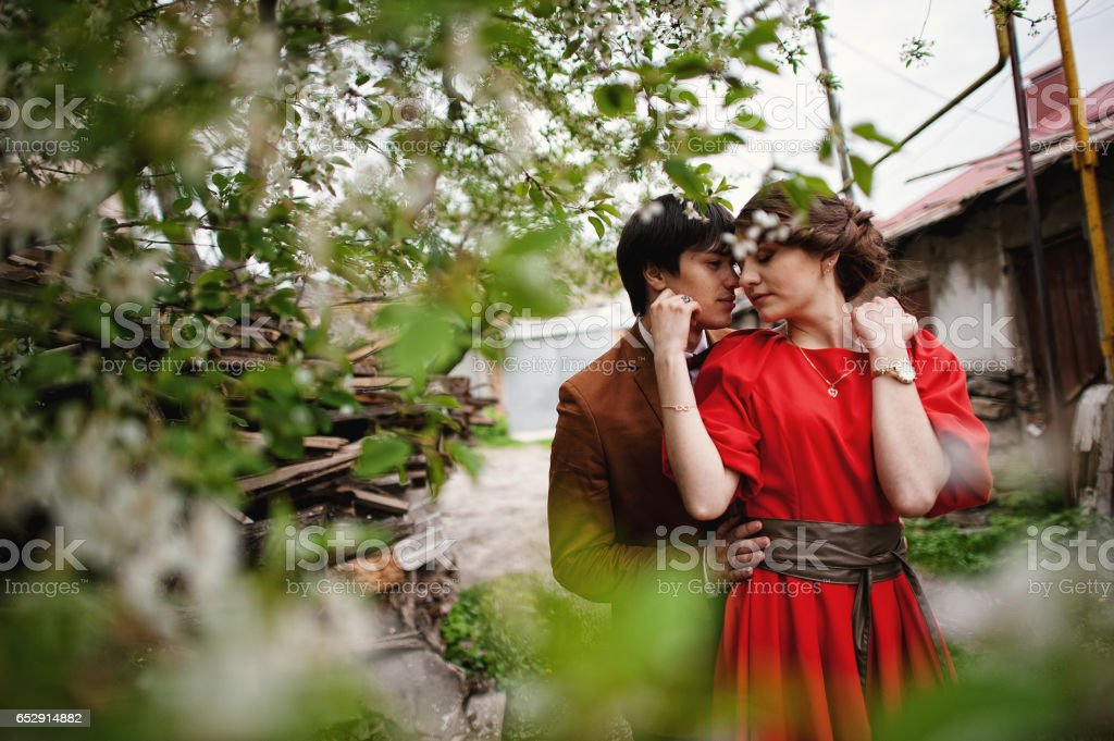 Couple hugging in love near blooming trees garden. Stylish man at velvet jacket and girl in red dress in love together stock photo