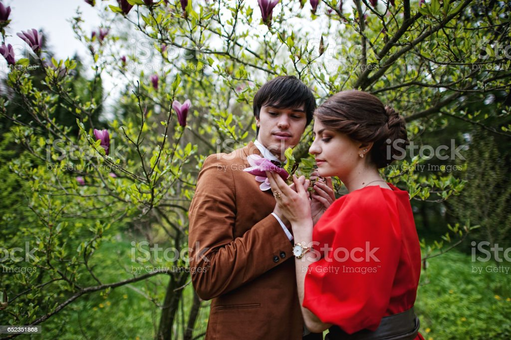 Couple hugging in love near magnolia tree. Stylish man at velvet jacket and girl in red dress in love together stock photo