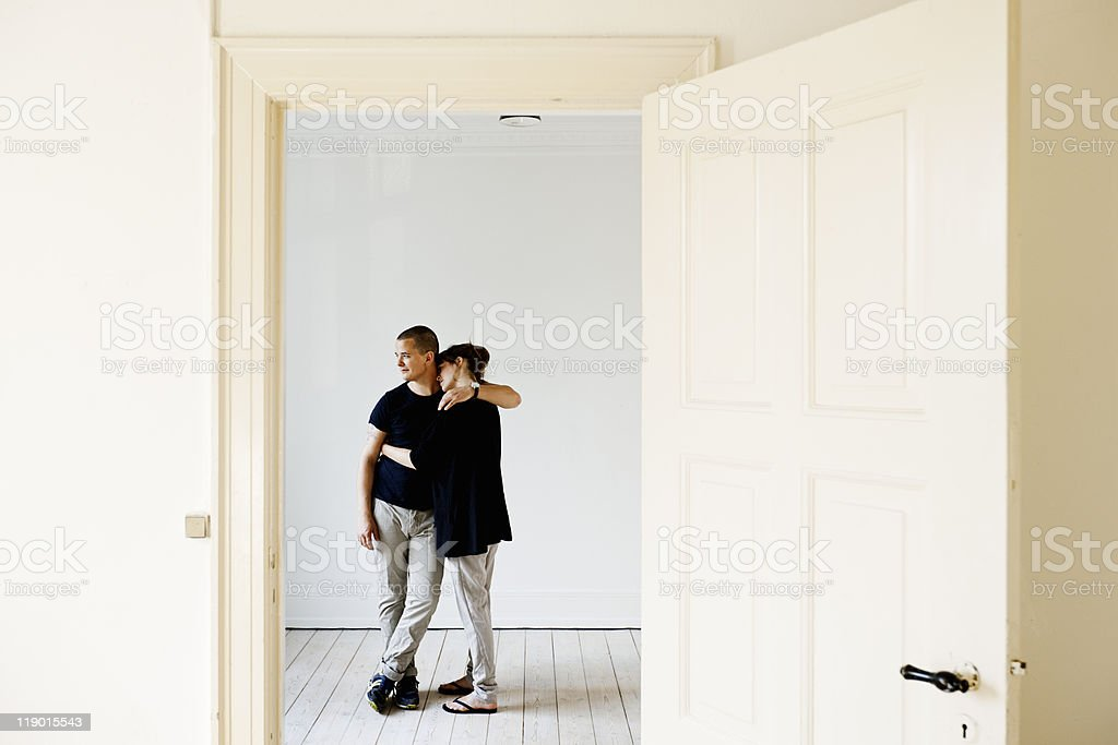 Couple hugging in new home stock photo