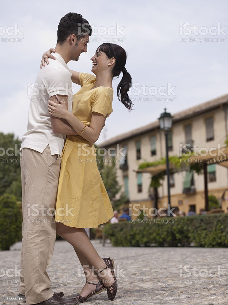 Couple hugging in urban plaza stock photo