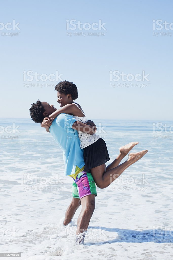 Couple hugging in waves at beach royalty-free stock photo