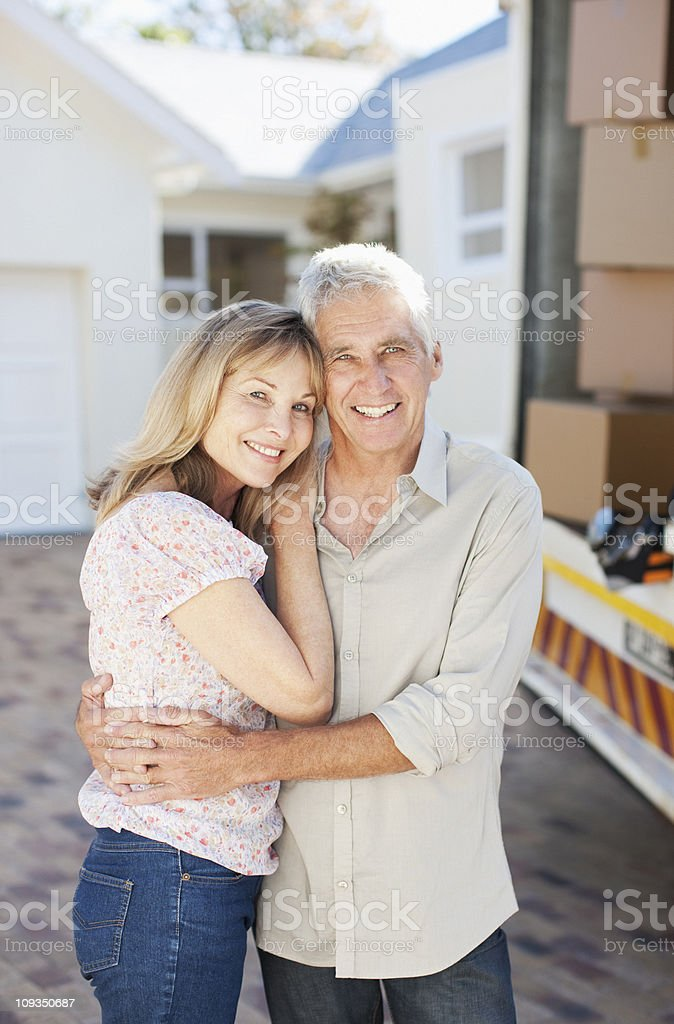 Couple hugging near moving van and new house royalty-free stock photo