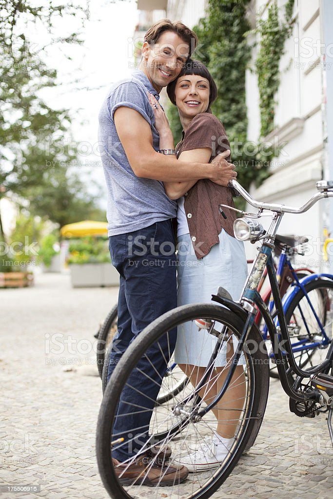 Couple hugging next to bicycles stock photo