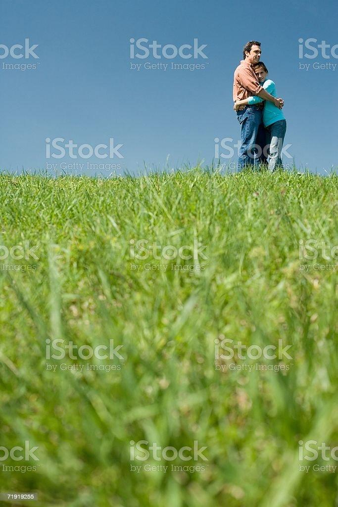 Couple hugging on field stock photo