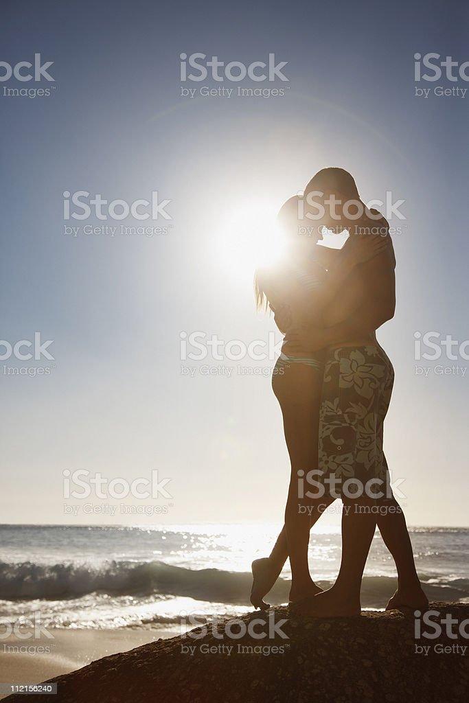 Couple hugging on rock near ocean royalty-free stock photo