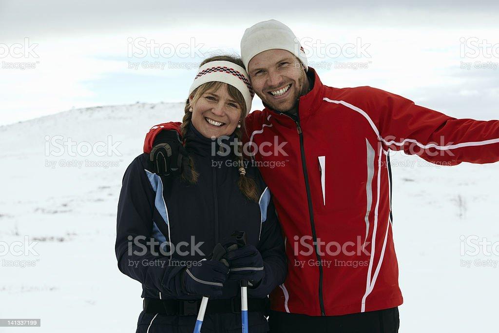 Couple hugging on snowy mountain stock photo