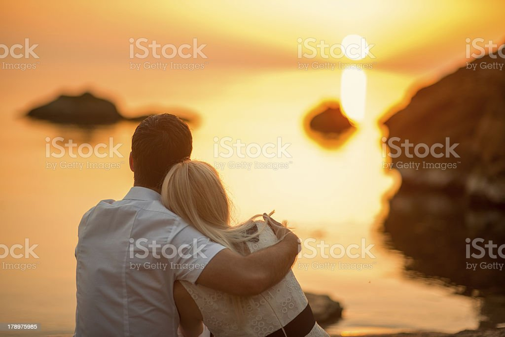 couple hugging on the beach at sunrise stock photo