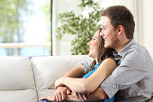 Couple hugging sitting on couch at home