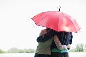 Couple hugging underneath red umbrella