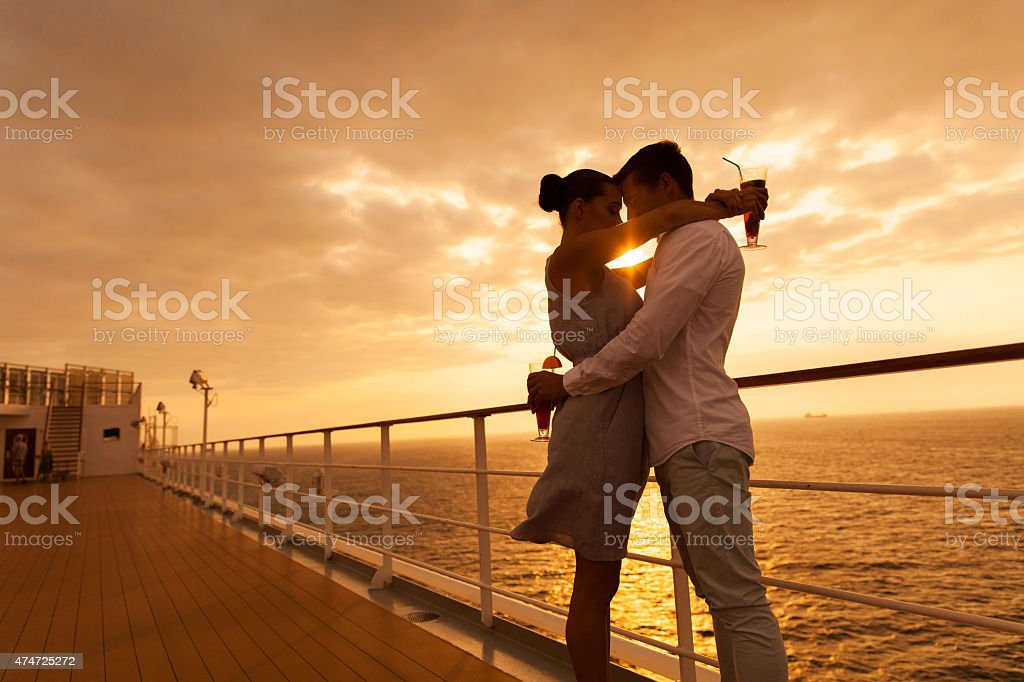 couple hugging with eyes closed at sunset on cruise stock photo