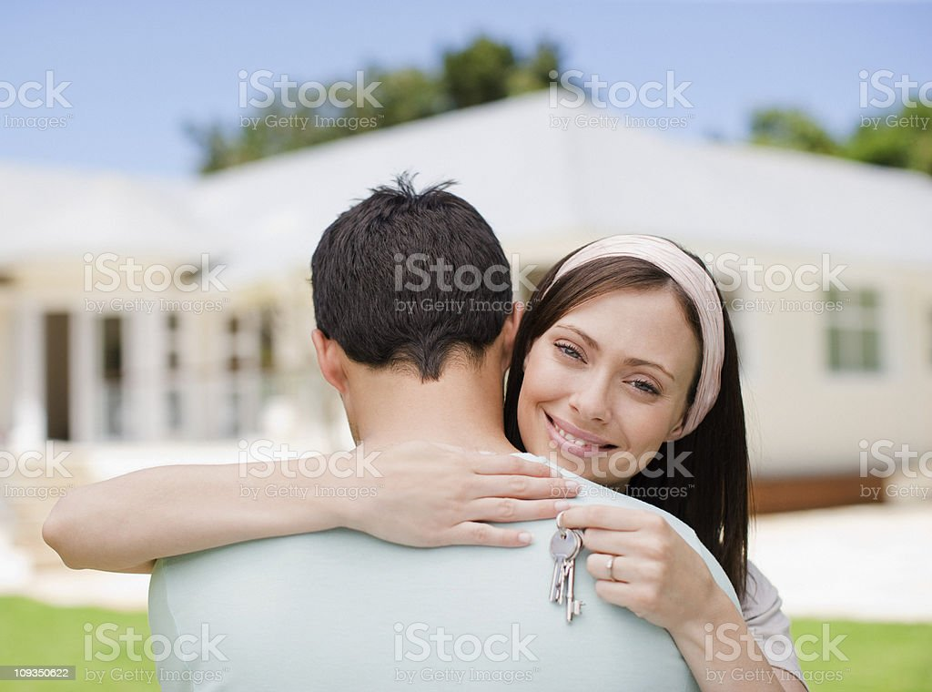 Couple hugging with keys to new house royalty-free stock photo
