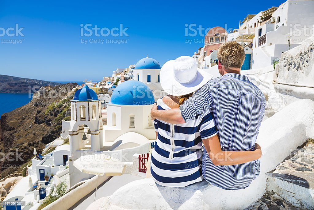 Couple hugs overlooking Santorini Island, Greece stock photo