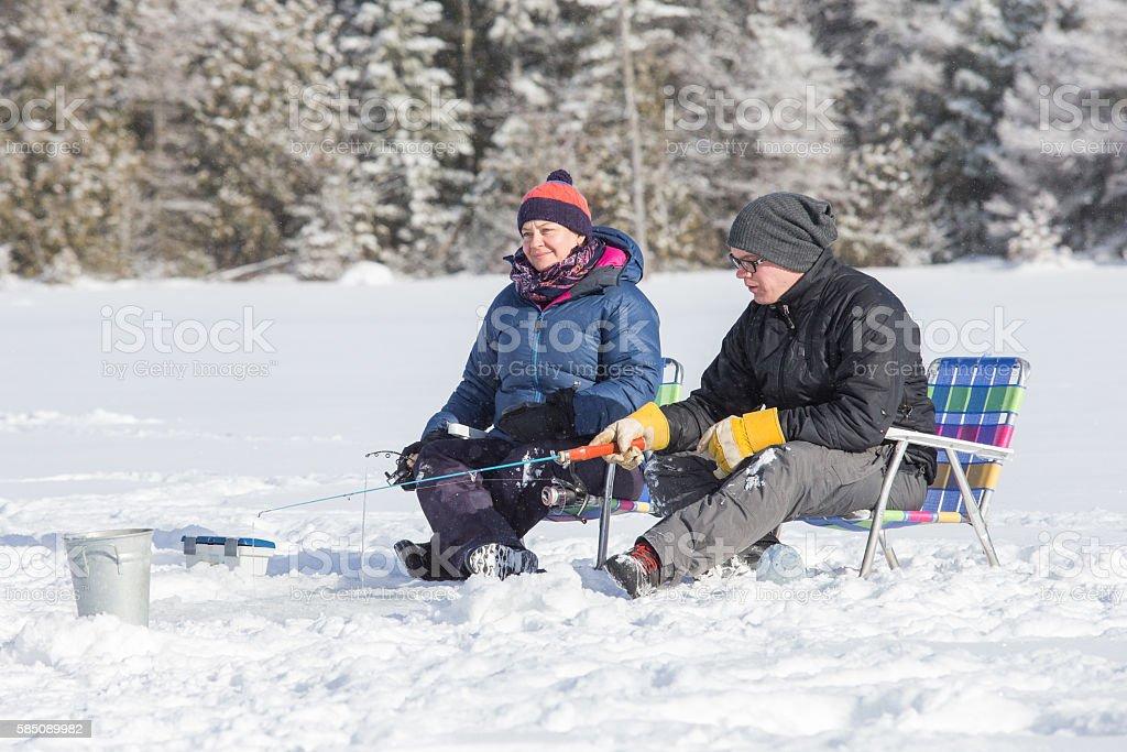 Couple ice fishing stock photo