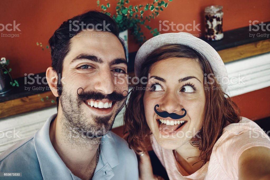 Couple in a bar gesturing for selfie stock photo