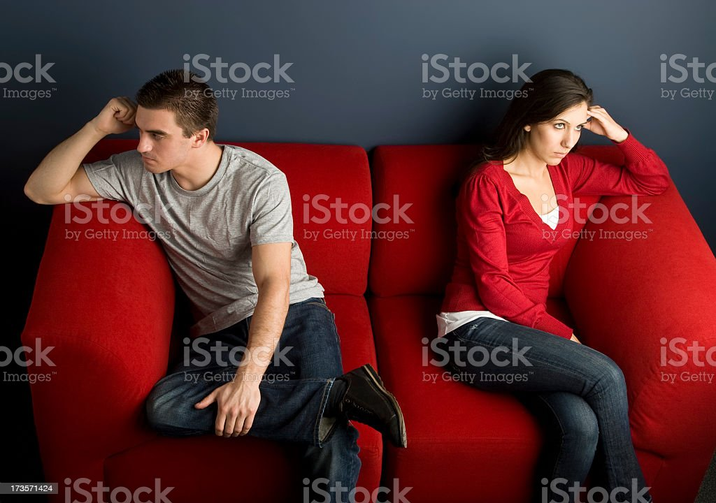 A couple in a little disagreement sitting on red couch royalty-free stock photo