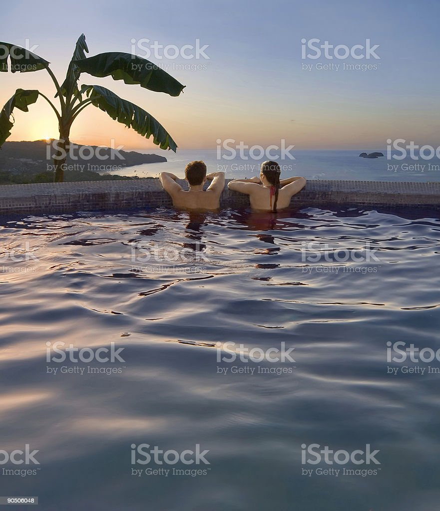 Couple in a pool near a tropical beach at sunset stock photo